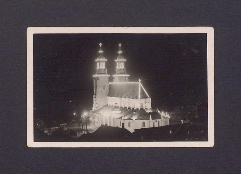 Widok z Rynku na odświętnie iluminowaną bazylikę.